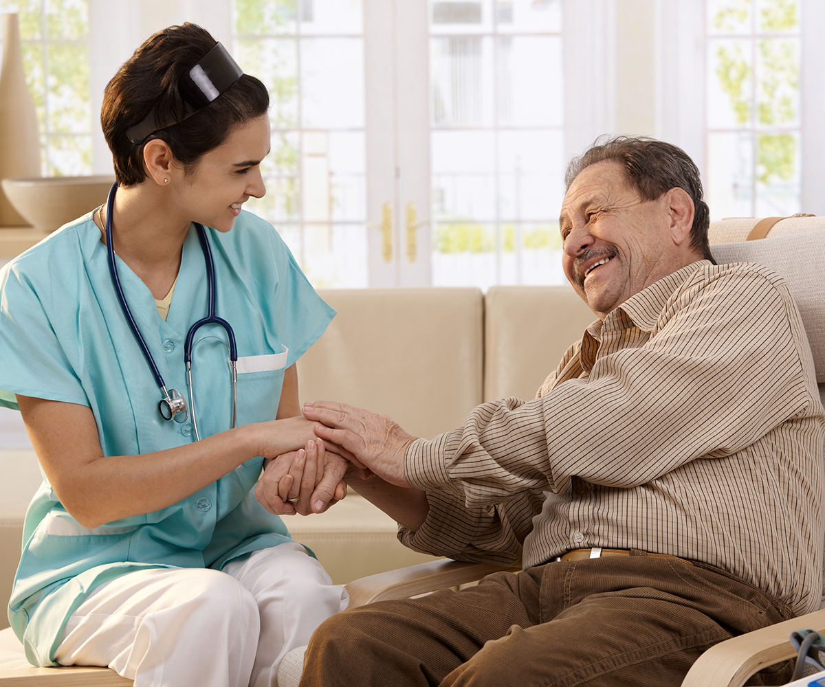 Happy nurse holding hands of elderly patient sitting side by side at home, laughing.